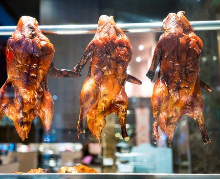 A look through roasted duck hanging in the metal bar within chinese restaurant.