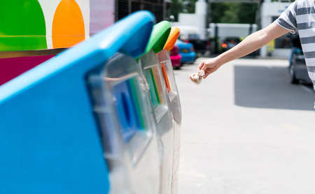 Woman hand putting used paper in recycled bin at parking area. Different color trash cans in row for waste management. Perspective disposal view for saving environmental concept.