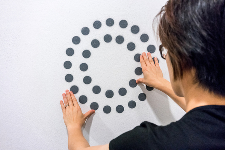 hand touch: Woman using hands with dot graphic and circle diagram on white wall. Business info graphic interface design concept.