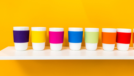 Row of white ceramic cup with colorful pantone silicone cup holder on white shelf against yellow background. Minimal concept for decoration.