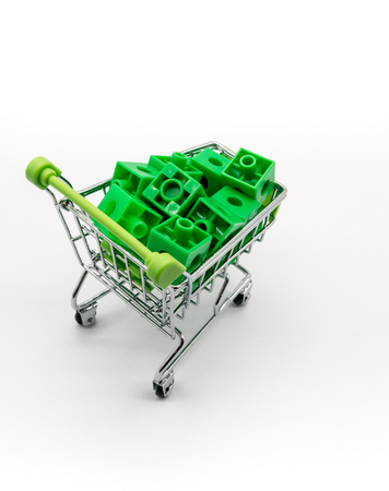 carrying: Green shopping cart with green 3d puzzle inside. Go Green concept. Stock Photo
