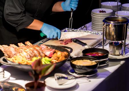 Chef d'hôtel tranchant une côte de boeuf grillée avec un long couteau et une fourchette à la station de découpage. Rare niveau de steak cuit. Banque d'images - 82871940