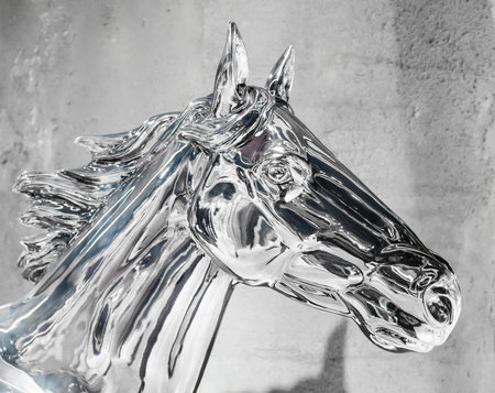 iron horse: Head of silver horse statue. Shiny metal knight with reflection against painted wall for decoration. Sign of spirit and pride.