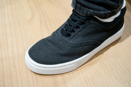 Black canvas sneaker under dark boot cut jeans on clean wooden floor texture. Basic casual shoe for new generation fashion.