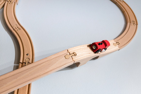 hobbyist: Red train toy on plastic wooden track isolated on white background