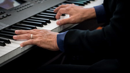 Pianist playing electric piano in concert, music concept