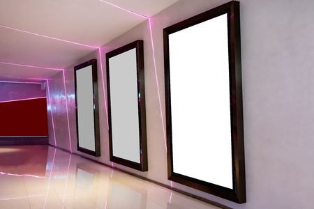 Three movie poster frames along the walkway in modern interior design for movie theater