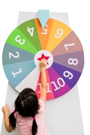 Chica asiática tratando de girar la enorme rueda de fortuna colorido con números de dígitos blancos aislados sobre fondo blanco Foto de archivo - 84206277