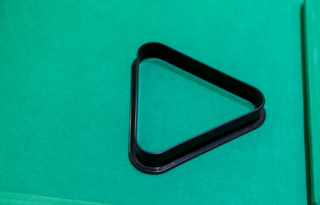 a black plastic pool and snooker triangle on green table