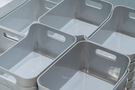 Stack of grey plastic trays arrangement for background. Multi-purpose kitchenware collection