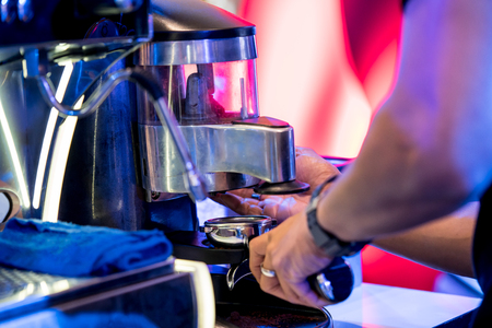 Hand dosing fine ground coffee from the grinder for making perfect espresso shot. Stock Photo