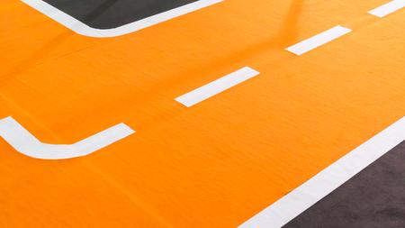 Curve van oranje renbaan en rijstroken. Tijdelijk instellingsdetail op tapijtvloer.