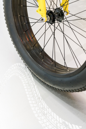 Black rubber tire of bicycle wheel with curve reflection of tire pattern on white polished stone floor.