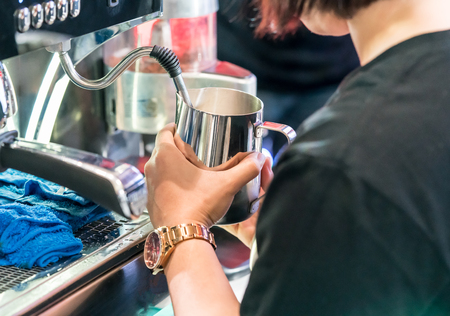 Asian barista steaming fresh milk in stainless pitcher with vent pipe from coffee machine.