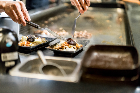 Hand of Chef cooking salad on hot pan in front of customers. Japanese Tepanyaki Steak