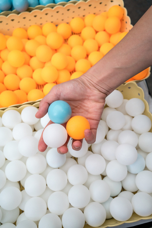 Hand holiding three different colors of ping-pong balls.
