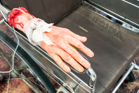Bloody and creepy halloween toy, fake human hand tied with saline drip on wheel chair for halloween hospital theme.