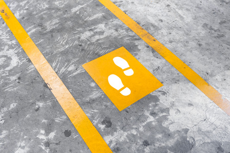 Walkway lane in parking building. Painted yellow footsteps between parallel yellow lines on abstract cement floor. Step by step concept. Stock Photo