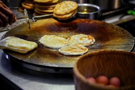 Vendor hand frying round roti dough in hot pan with vegetable oil by street.