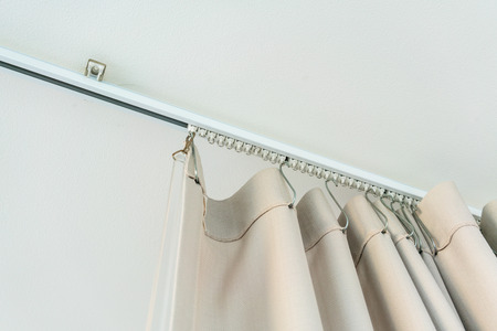 White curtain rail system with light brown curtain installed on white ceiling Stock Photo