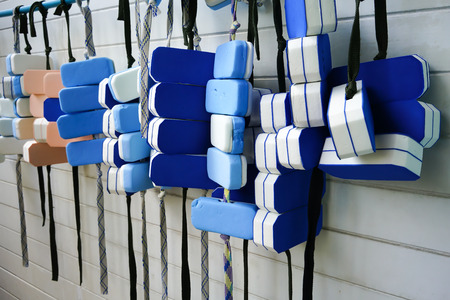 A row of swimming belts hanging on PVC bar by swimming pool against white pattern wall. Buoyancy equipment for beginner training.