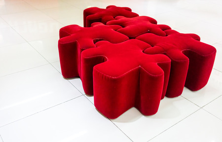 Red fabric jigsaw stools suitable for unique entertainment interior isolated on white tile floor. Stock Photo