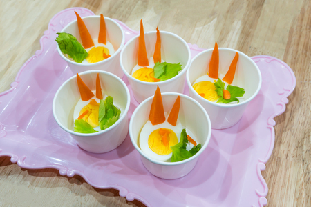 sample tray: Food samples in small paper tasting cup on vintage pink tray. Cute decorative rabbit from boiled egg and vegetable for kid healthy party.