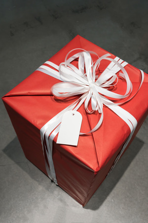 Red wrapped present box with white fancy bow tie and blank greeting tag against concrete background