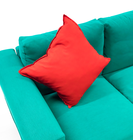 Red cotton square pillow on green fabric sofa isolated on white background.
