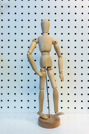 3D wooden figure posing walking action isolated on white perforated background. Stock Photo