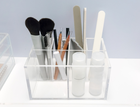 Clear acrylic holder in square shape applied for beauty organizer on white table against grey wall background.