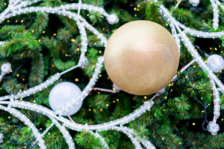 Hanging shiny golden ball and silver Christmas wreath with tinsel and ornaments for seasonal greeting.