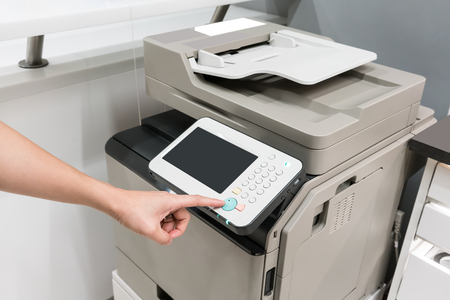 Womans hands pressing button on copy machine in office or store