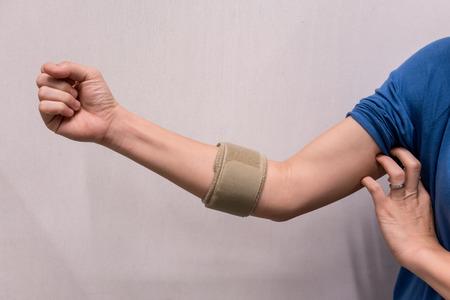 Asian woman wearing elbow brace to reduce pain