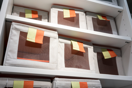 Fabric storage boxes in square shape with orange and yellow pull to open tag arranged on white shelf. Idea for home organizer.