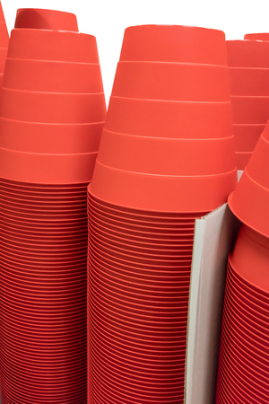 Stacks of red plastic buckets in white corrugated boxes isolated on white background with path selection Stock Photo