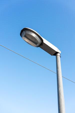 Street Lighting Technology against blue sky background. Light Pole Closeup. Фото со стока