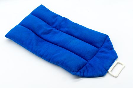 白い背景に隔離された青いマイクロ波暖房パッド。肩、首、背中、体の痛みの軽減療法のための冷たく、熱いラップ。