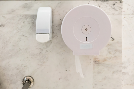 White plastic toilet tissue roll holder and toilet seat cleaner dispenser mounted on marble wall.