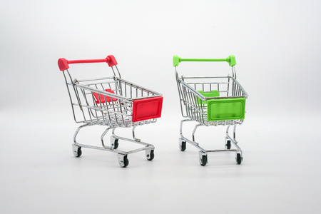 Green and red miniature shopping carts isolated on white background