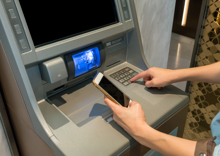 Asian woman looking at mobile phone display while pressing digit buttons on brown ATM machine.