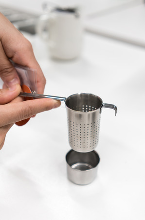 Woman hands holding stainless steel tea infuser with dish set isolated on white table.