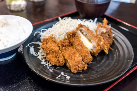 Closed up deep fried pork cutlet coated with flaky panko bread crumb and stuffed with cheese, Pork Tonkatsu over shredded cabbage