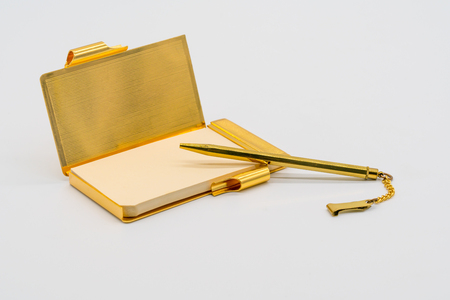Gold personal vintage notebook case with pen isolated on white background.