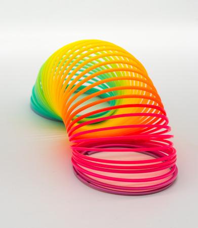 Stuk speelgoed van de regenboog het Slinky die lente op witte achtergrond wordt geïsoleerd.