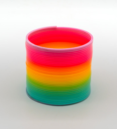 Rainbow Slinky spring toy isolated on white background. Stock Photo