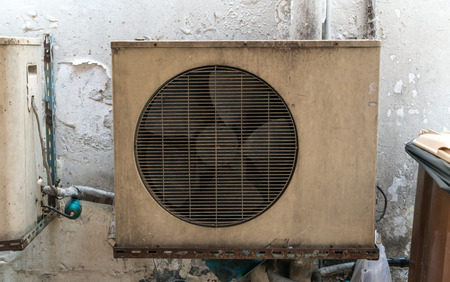 Old vintage rusting metal exterior fitted airconditioning unit mounted on wall needing maintenance