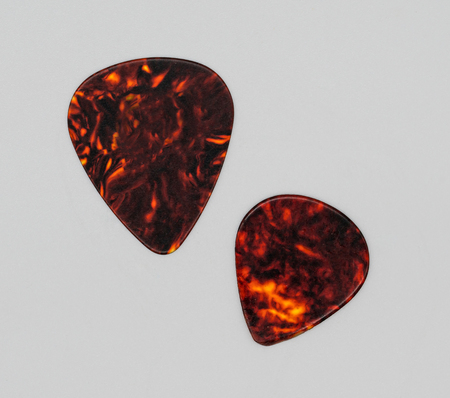 Two different sizes of brown plastic guitar plectrum isolated on white background. Guitar Picks