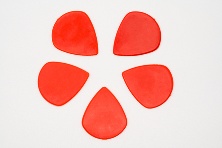 Red plastic guitar picks isolated on white background. Stock Photo