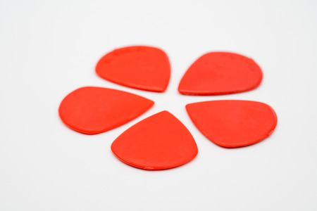 Red plastic guitar picks isolated on white background with shallow depth of field